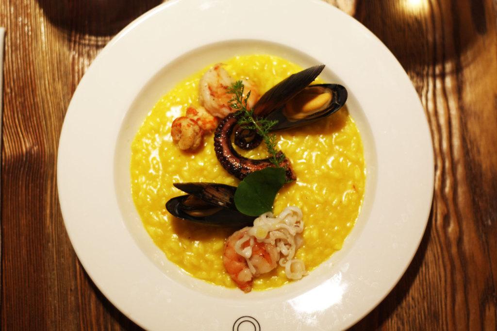 Risotto z owocami morza: ryż z szafranem, sosem ostrygowym, a do tego kalmary, małże i krewetki.